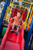 2 year old mixed race boy plays in playground. A smiling 2 year old mixed race boy plays on a red slide in an outdoor playground Royalty Free Stock Photos