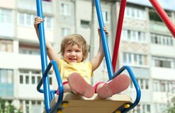 2 years child on swing. Against urban landscape royalty free stock images