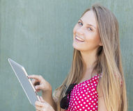 20岁接触片剂计算机和微笑的女孩 免版税库存照片