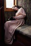 20世纪初读书米黄葡萄酒礼服的少妇  库存图片