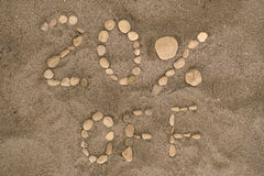 20 Percent Off. Pebbles on a beach arranged to spell out 20% OFF stock image