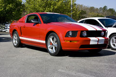 2008 Ford Mustang GT Red. 2008 Ford Mustang GT, red with white top and side racing stripes. Bullet wheels, side louver and fog lamps royalty free stock images