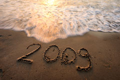 2009 on the Beach. Number 2009 engraved on the surface of beach sand with incoming waves on the top stock image