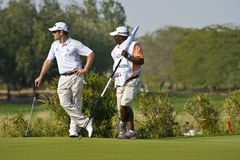 2009 Commercial Bank Qatar Masters tournament. South African player Oosthuizen and his caddy studies the field of play in the 2009 Commercial Bank Qatar Masters Stock Image