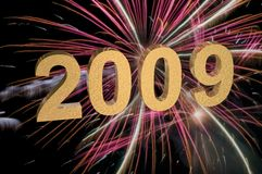 2009 With Fireworks. Year 2009 with exploding pink fireworks in background. 2009 numerals are gold with reflective textured front and sides creating a metallic stock illustration