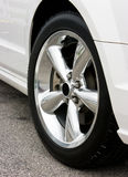 2009 Ford Mustang Bullitt Wheel. Closeup of a 2009 Ford Mustang polished chrome bullitt wheel mounted on a white automobile Stock Photo