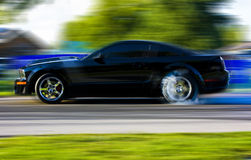 2009 Ford Mustang Race Car in Motion. 2009 Ford Mustang race car burnout.  Black coupe with side stripe, cowl hood and chrome racing wheels shown with motion