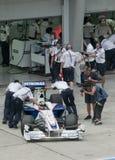 2009 Nick Heidfeld at Malaysian F1 Grand Prix. SEPANG, MALAYSIA - APRIL 3 : Mechanics push Nick Heidfeld's car of BMW Sauber F1 Team during practice session at Royalty Free Stock Photography