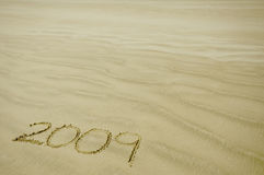 2009 in the sand. 2009 written in the sand with background of waves and blue sky Royalty Free Stock Photos