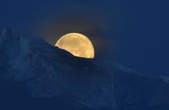 2011 ajustes super da lua atrás do pico dos piques Fotografia de Stock Royalty Free