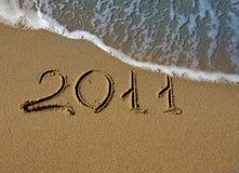 2011 - Die Beschreibung auf dem Sand in dem Meer Lizenzfreie Stockfotografie
