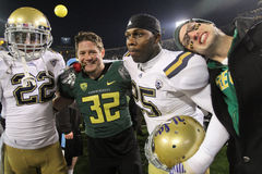 2011 PAC-12 Championship Game. Oregon and UCLA players, along with a randon Oregon fan, pose at the finish of the inaugural Pac-12 Championship game at Autzen Royalty Free Stock Images