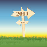 2011 sign. A wooden sign showing the way to 2011 from 2010. Sun setting on 2010 concept royalty free illustration