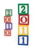 2011 Wood Blocks. Wooden alphabet blocks stacked to form '2011', representing the new year. Blocks stacked to form '2010' are out of focus in the background Royalty Free Stock Image