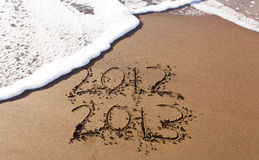 2012 and 2013 written in sand with waves Royalty Free Stock Image