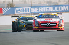 2012 Dunlop 24 Hours Race in Dubai. DUBAI - JANUARY 14: Race winner, a Mercedes SLS AMG GT3 in front of last year's winner, a BMW Z4 GT3, during the morning royalty free stock photography