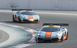 2012 Dunlop 24 Hours Race in Dubai. DUBAI - JANUARY 13: Two Lamborghini Gallardo LP600 in Gulf livery coming through curve 1 during the 2012 Dunlop 24 Hour Race royalty free stock image