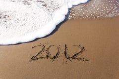 2012 geschreven in zand met golven Stock Afbeelding