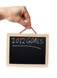 2012 goals. On blackboard held by hand over white background Stock Photos
