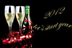 2012 let?s start year. Detail of two glasses near a middle bottle of champagne on black background with space for text Royalty Free Stock Image