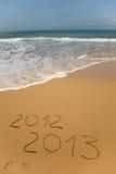 2012 och 2013 som skrivs i sand Fotografering för Bildbyråer