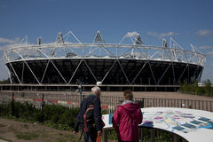 2012 Olympic Previews. Preview images for the London 2012 Olympic games. Tourists study a large map of the Olympic Village, with the main Stadium in the Royalty Free Stock Photography