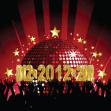 2012 Party. Crowd partying in front of sparkling red disco ball with 2012 sign Stock Photography