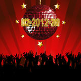 2012 Party. Crowd partying under a sparkling red disco ball with 2012 sign Royalty Free Stock Photo