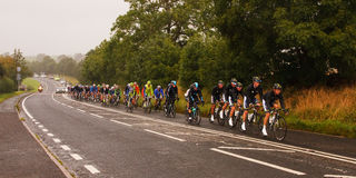 The 2012 Tour of Britain. Stage 4 of the 2012 Tour of Britain professional bicycle race.  The peloton heads along the A6 and through Plumpton, Cumbria in Royalty Free Stock Images