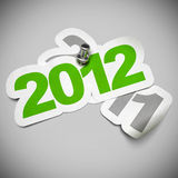 2012 versus 2011 green sticker. 2012 green sticker fixed onto 2011 - 3d greeting card over a grey background, numbers are fixed with a metal thumbtack Stock Photos