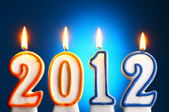 2012 year. 2012 burning candles close-up over blue backgroumd Stock Photos