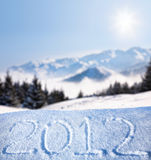 2012 year on the snow. 2012 new year message on the snow at mountain and blue sky with sun background Royalty Free Stock Image