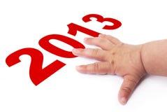 2013 anos novos e mão do bebê Imagem de Stock