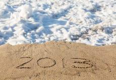 2013 i sanden som täckas av havet, vinkar Arkivfoto