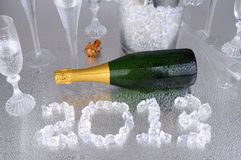 2013 in Ice with Champagne. Happy New Years. 2013 spelled out with ice cubes on a wet metallic surface, surrounded by a champagne bottle, and flutes stock photos