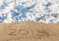 2013 na areia que está sendo coberta por ondas do mar Foto de Stock