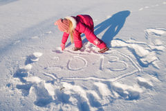 2013 in the snow. A little girl writes 2013 in the snow stock photography