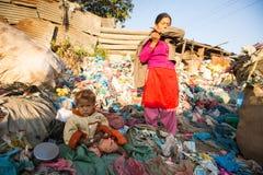 未认出的孩子在加德满都坐,当她的父母工作在转储时, 2013年12月22日,尼泊尔 免版税库存照片