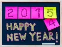 新年快乐2015年在黑板写的消息手,在便条纸陈述的数字,替换2014年的2015年 免版税库存照片