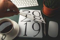 2018 поворачивает, 2019 раскрывает на блокноте мужской рукой на темной таблице работы как предпосылка Нового Года дела стоковое фото rf