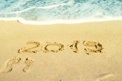 2019 inscription written on sandy beach with wave approaching. Stock Photo