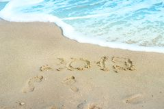 2019 inscription written on sandy beach with wave approaching. Stock Image