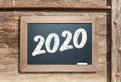 2020 Written On Slate Chalk Board Against Aged Wood And Pipe Background Stock Image