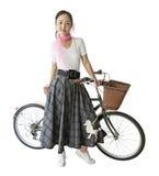 20世纪50年代的妇女穿衣与减速火箭的自行车的 库存图片