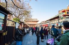 Токио, Япония - 21-ое ноября 2013: Туристы ходя по магазинам на торговой улице Стоковое Изображение