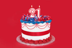 21st Cake. Twenty-first Birthday Cake, with numeral candles, on vibrant red background Stock Photography