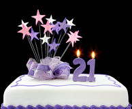 21st Cake. Cake with number 21 candles. Decorated with ribbons and star-shapes, in pastel tones over black background stock photography