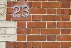 23 Hausnummer auf Backsteinmauer Stockfoto