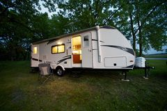 25 Feet Travel Trailer. Modern 25 Feet Travel Trailer - Camping in the Forest in the evening or dusk. Recreation Photo Collection stock photography