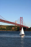 25th April bridge. Over river tagus (tejo) with view to christ statue in Lisbon, Portugal Stock Photography